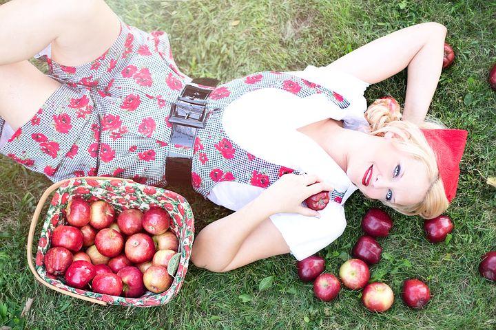 Eine junge Frau vom Land liegt glücklich im Gras