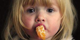Ein kleines Weihnachtsmädchen mit einem Stück Mandarine im Mund